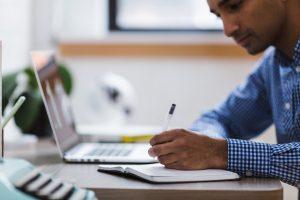 Suchmaschinenoptimierer mit Laptop und Schreibblock
